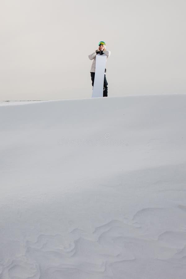 Junge Frau und ihr Snowboard auf schneebedecktem Bergabhang lizenzfreies stockbild