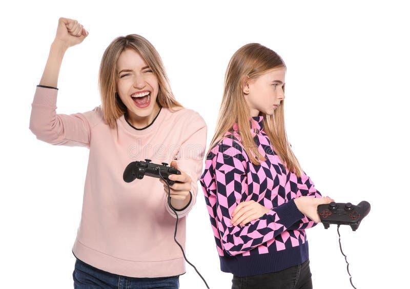 Junge Frau und Jugendliche, die Videospiele mit Pr?fern spielt stockfotografie