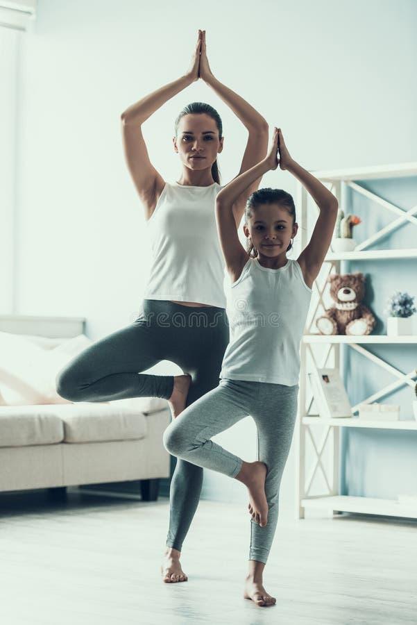 Junge Frau und kleine das Mädchen, die Yoga tut, werfen auf stockbild