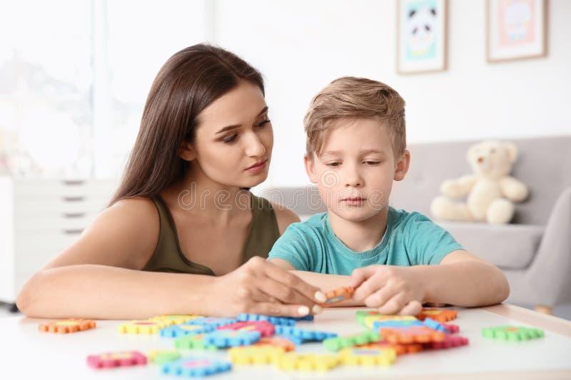 Junge Frau und kleiner Junge mit dem autistischen Störungsspielen stockfotografie