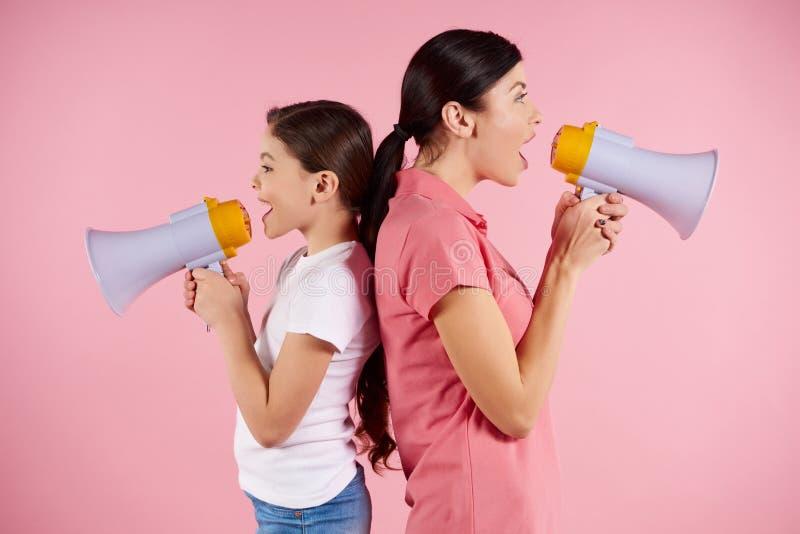 Junge Frau und Mädchen, die in den Megaphonen schreit lizenzfreie stockfotos