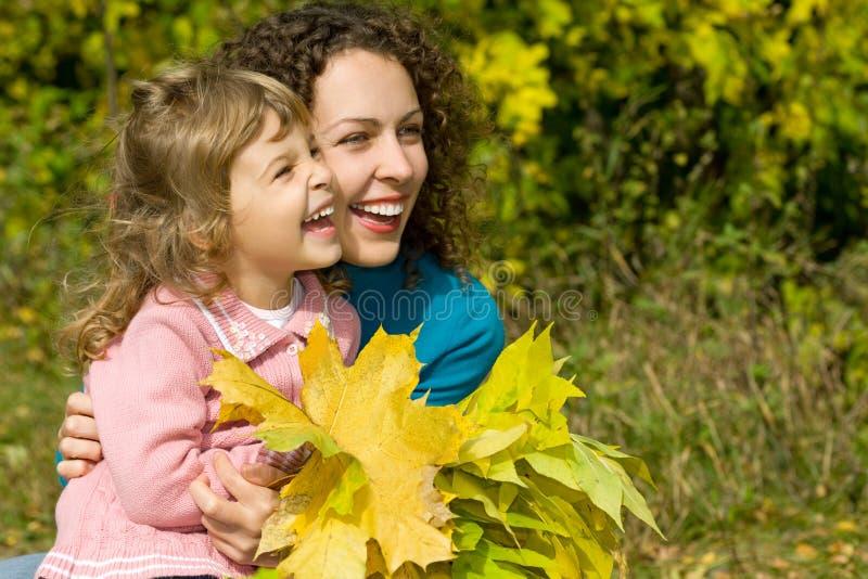 Junge Frau und Mädchen lachen mit Blättern im Garten stockbilder