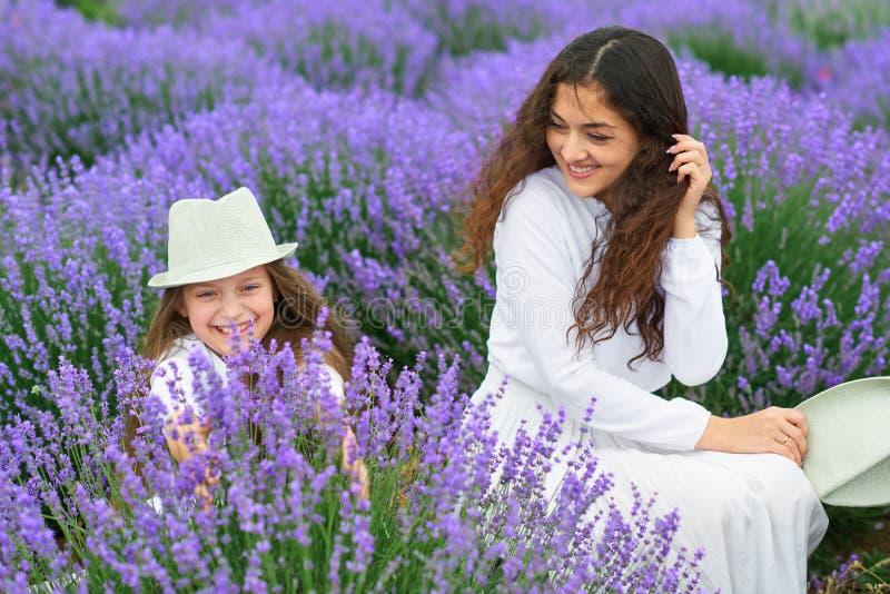 Junge Frau und Mädchen sind auf dem Lavendelgebiet, schöne Sommerlandschaft mit roten Mohnblumenblumen stockfotografie
