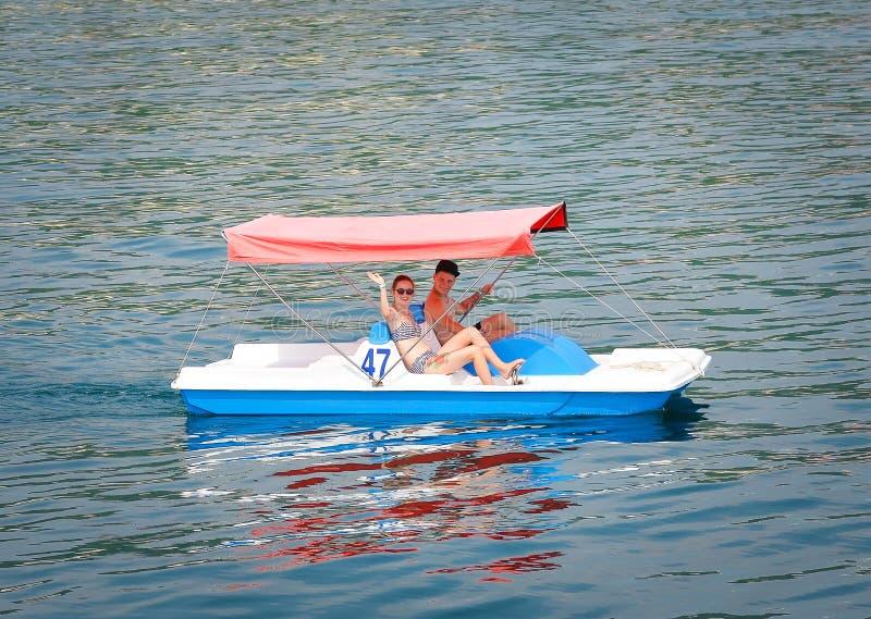 Junge Frau und Mann haben Spaß unter Verwendung des Wasserfahrrades lizenzfreie stockfotografie