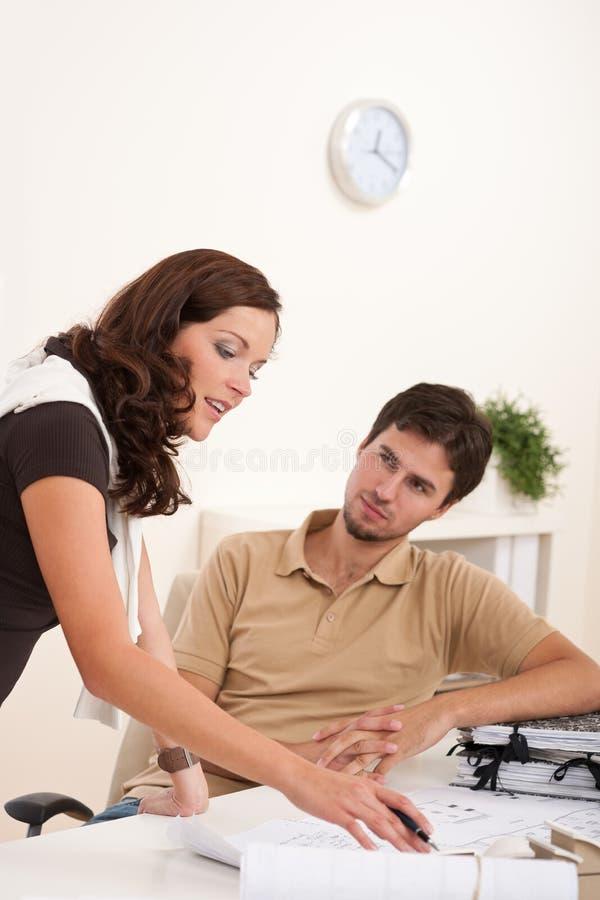 Junge Frau und Mann im Büro stockfotografie