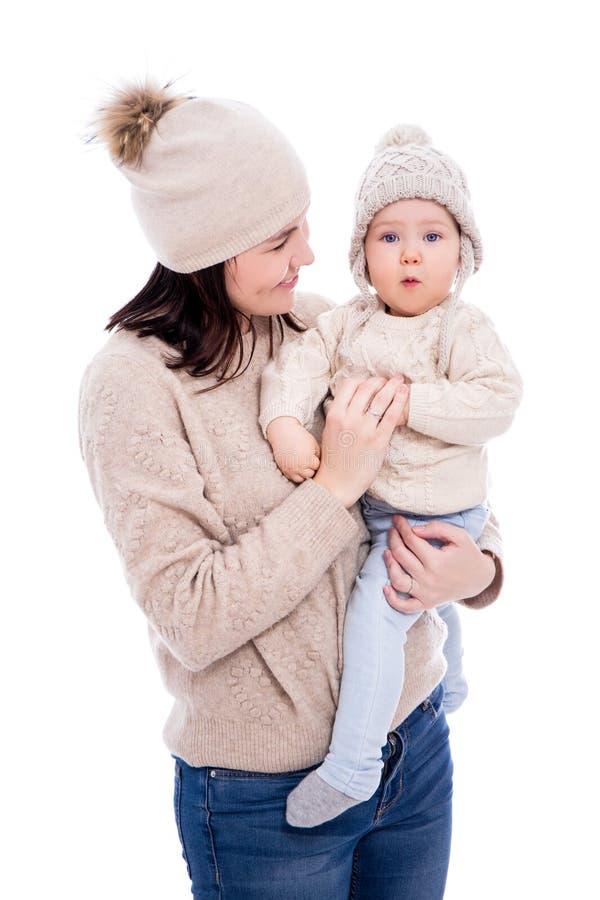 Junge Frau und nettes Baby in den woolen Strickjacken und in den Hüten des Winters lokalisiert auf Weiß lizenzfreie stockfotos