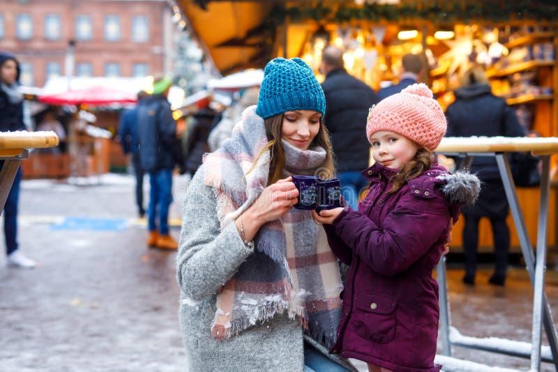 Junge Frau und nettes Kindermädchen mit Schale dämpfendem heiße Schokoladen- oder Kinderdurchschlag lizenzfreie stockbilder