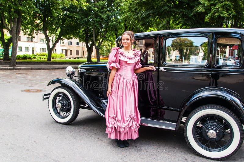 Junge Frau und Retro- Auto stockbilder