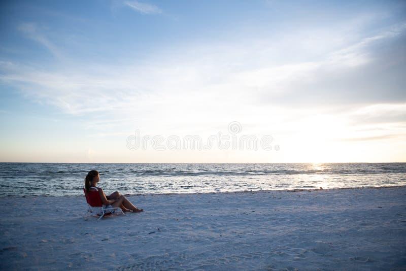 Junge Frau und Sonnenuntergang am Strand stockbild