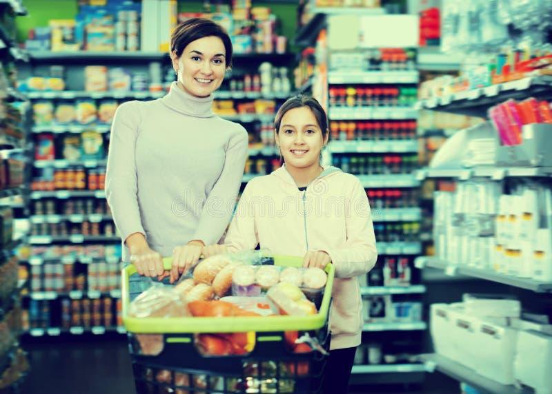 Junge Frau und Tochter mit Warenkorb stockfoto