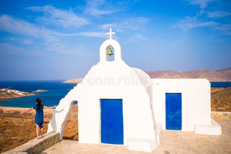 Junge Frau und traditionelle weiße Kirche mit Seeansicht in Mykonos-Insel, Griechenland lizenzfreies stockfoto