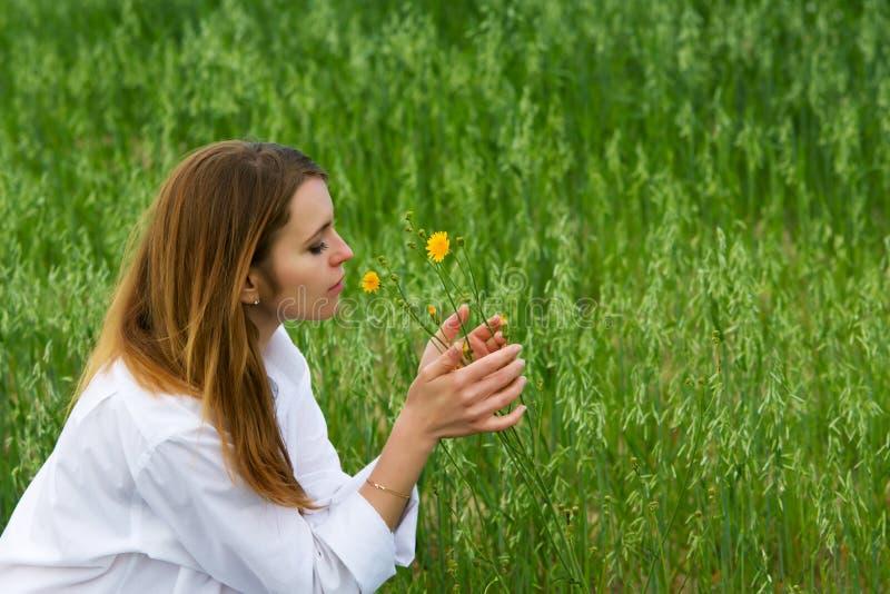 Junge Frau und wilde Blumen. lizenzfreie stockbilder