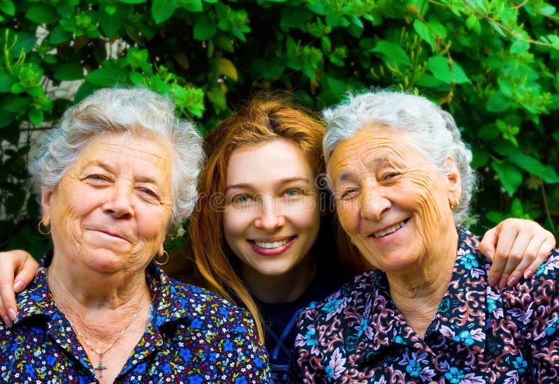 Junge Frau und zwei ältere Damen stockbild
