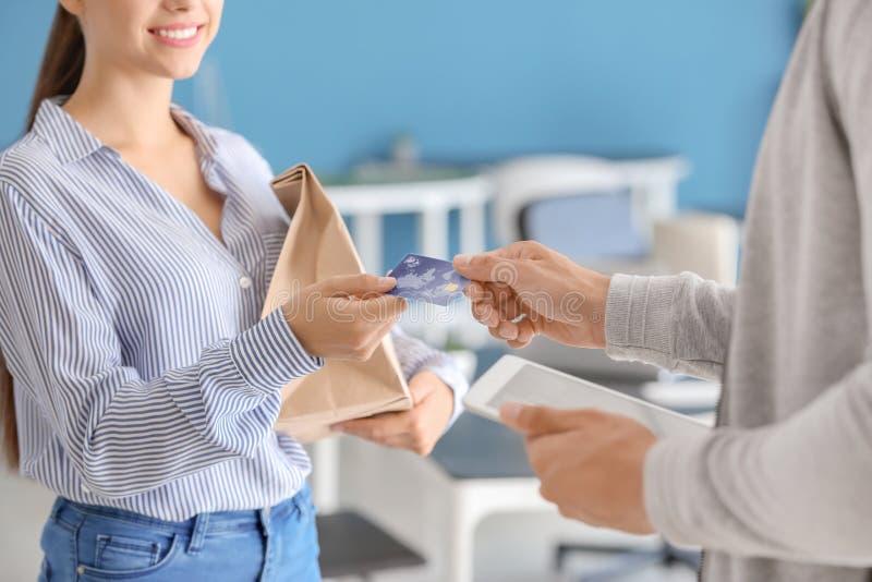 Junge Frau unter Verwendung der Kreditkarte, zum für Nahrungsmittellieferung zuhause zu zahlen stockfotos