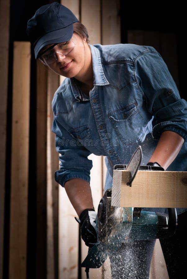 Junge Frau unter Verwendung der modernen elektrischen Säge in der Werkstatt stockbild