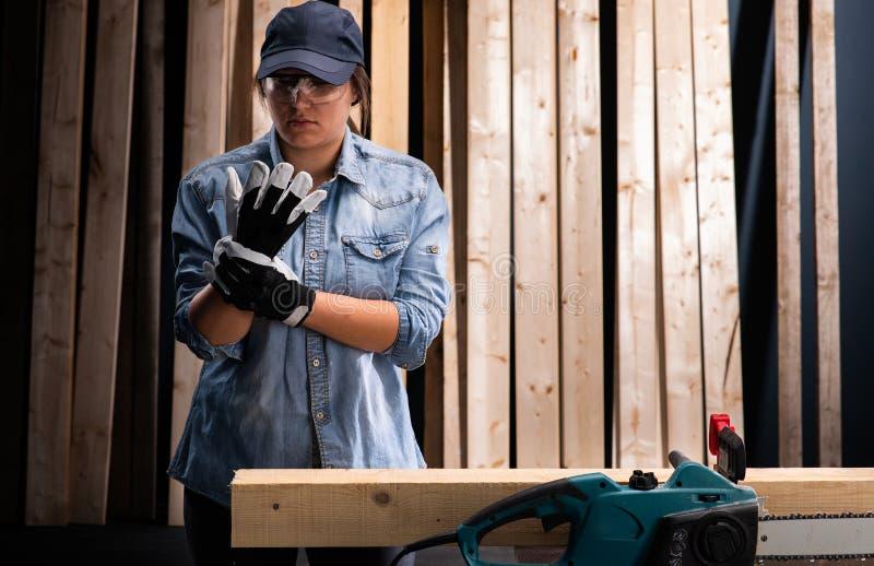 Junge Frau unter Verwendung der modernen elektrischen Säge in der Werkstatt lizenzfreies stockfoto