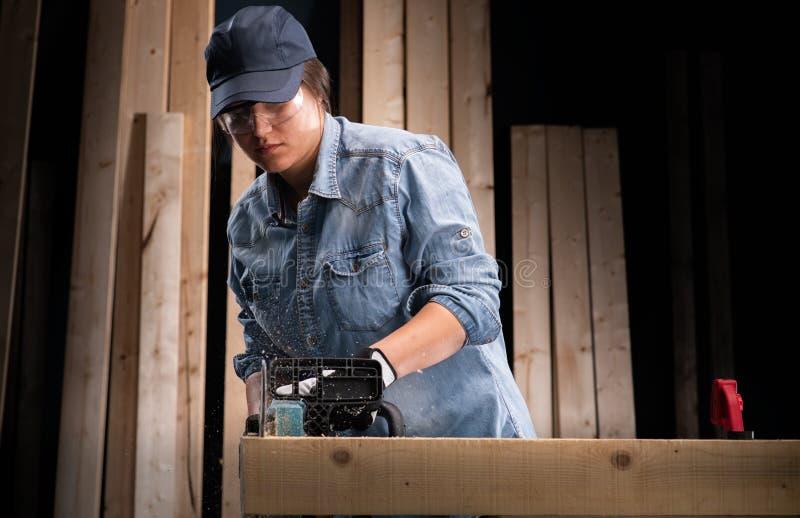 Junge Frau unter Verwendung der modernen elektrischen Säge in der Werkstatt lizenzfreies stockbild