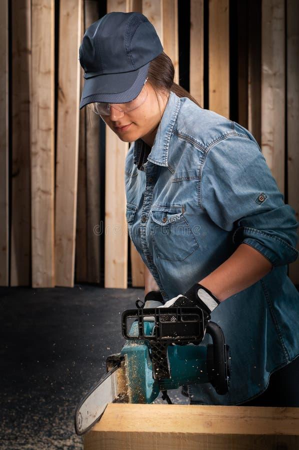 Junge Frau unter Verwendung der modernen elektrischen Säge in der Werkstatt stockfotos