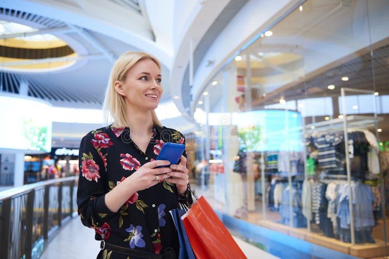 Junge Frau unter Verwendung des Handys im Einkaufszentrum lizenzfreie stockbilder