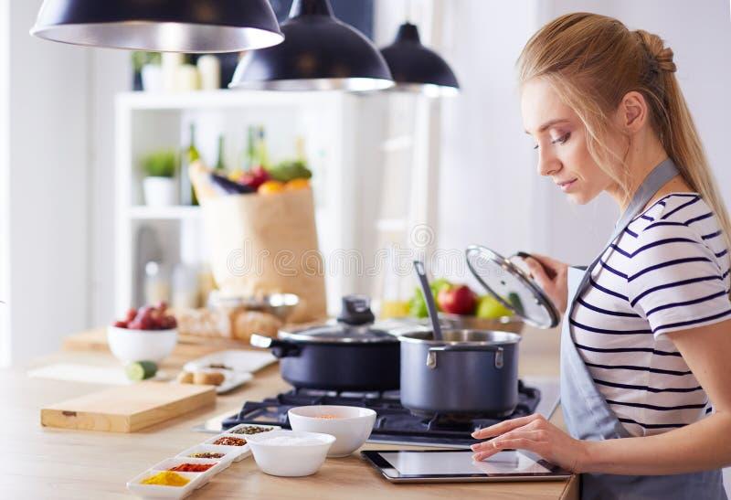Junge Frau unter Verwendung eines Tablet-Computers, zum in ihrer Küche zu kochen stockbilder