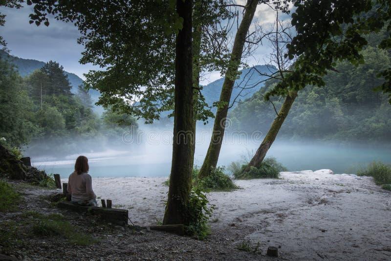 Junge Frau verlor im nebelhaften Zusammenströmen von Fluss Soca und Tolminka in Slowenien stockfoto