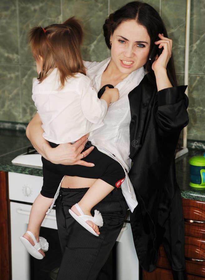 Junge Frau versucht, mit einem schreienden kleinen Baby zu Hause zu arbeiten stockfotografie
