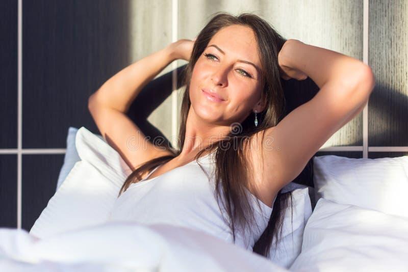 Junge Frau voll von Energie, wachend, Smilling auf und dehnen in Bett aus stockfoto