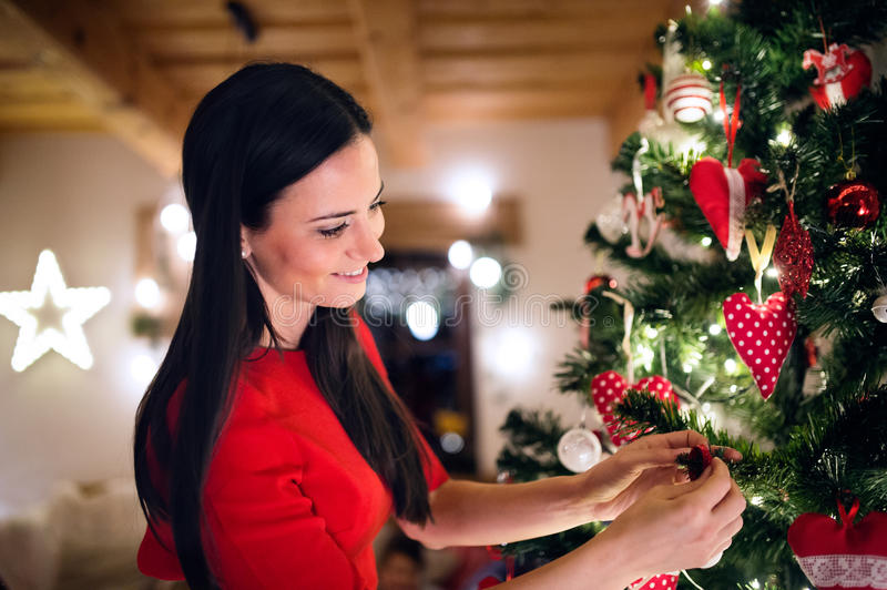 Junge Frau vor Weihnachtsbaum es verzierend stockfotografie