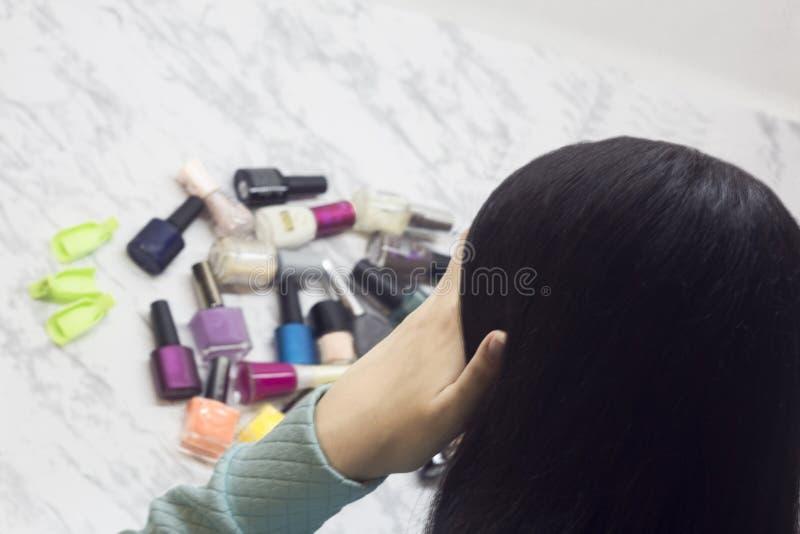 Junge Frau wählt Nagellacke, Schönheit und Mode, Schwierigkeit der Wahl, Dilemma, Badekurortsalon zu Hause stockfotografie