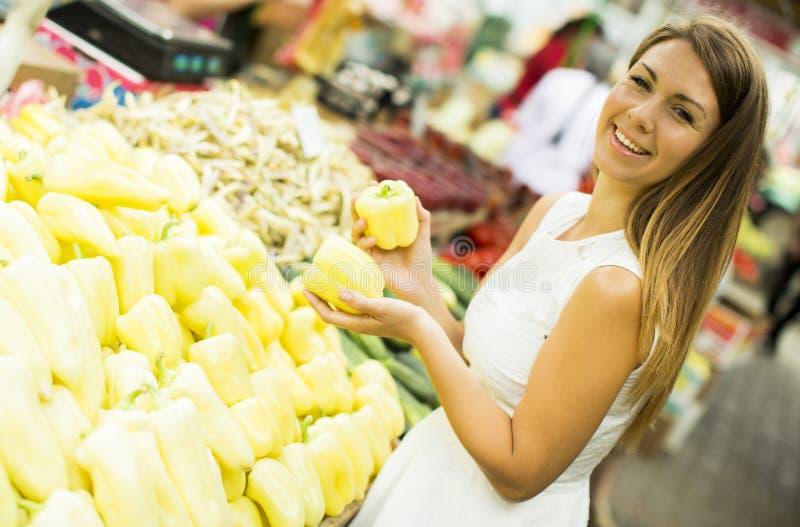 Junge Frau wählt und kauft gelbe Pfeffer am Markt stockfotografie