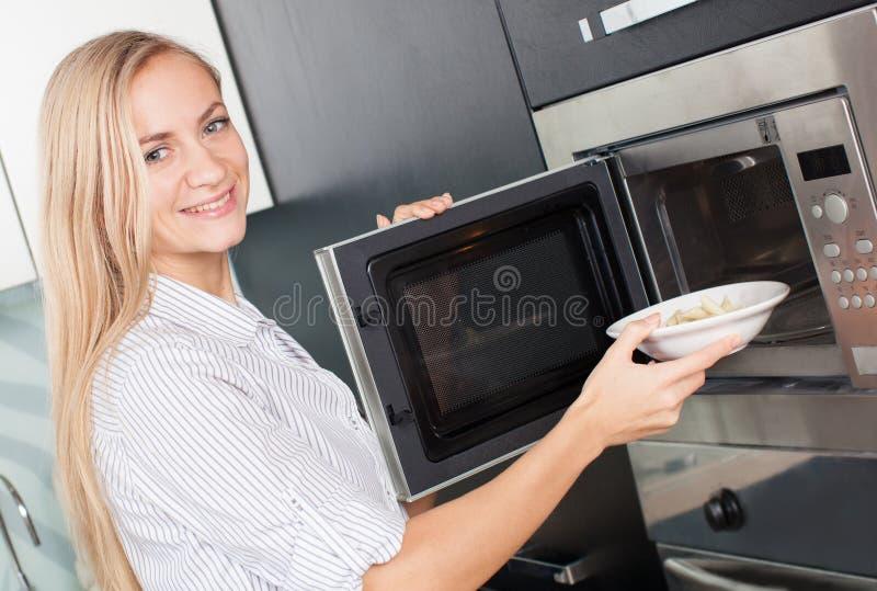 Junge Frau wärmt Lebensmittel in der Mikrowelle auf lizenzfreie stockfotos