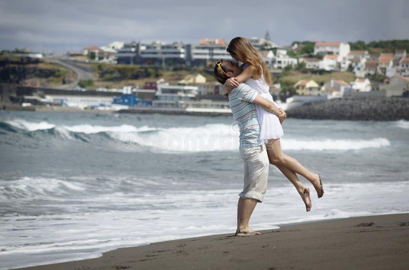 Junge Frau in weißes Kleideraufpassenden Meereswellen auf Sao-Miguel-Strand mit schwarzem voncanic Sand, junges Paar AzoresHappy  lizenzfreies stockfoto