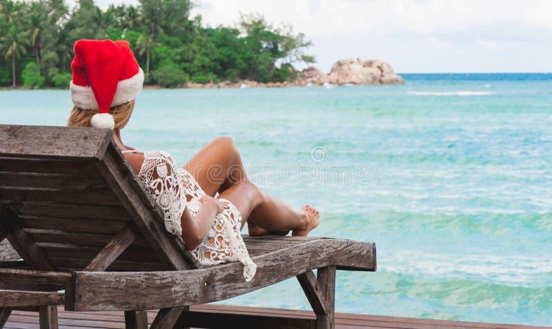 Junge Frau in Weihnachtsmann-Hut, der im Wagenaufenthaltsraum auf tropischem Seestrand sitzt stockfotos