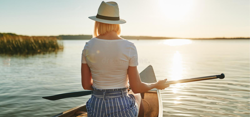Junge Frau, welche die Ansicht beim canoeing auf einem See genießt lizenzfreies stockfoto