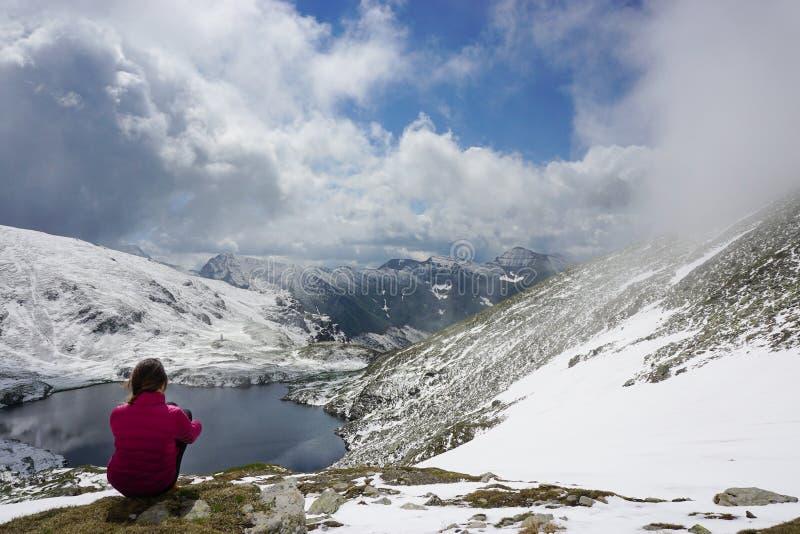 Junge Frau, welche die Ansicht in die Berge bewundert stockbilder