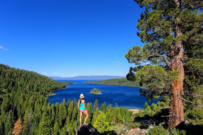Junge Frau, welche die Ansicht von Emerald Bay bei Lake Tahoe, Cali genießt stockfotografie