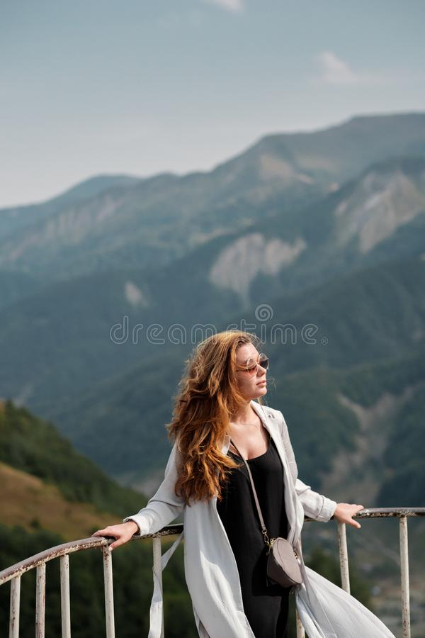 Junge Frau, welche die Ansicht von kaukasischen Bergen in Gudauri, Georgia genießt stockbild