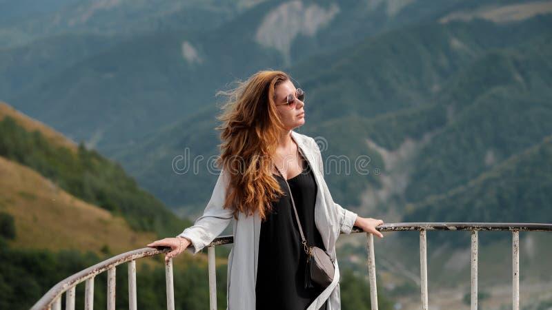 Junge Frau, welche die Ansicht von kaukasischen Bergen in Gudauri, Georgia genießt Ein Mädchen mit Gläsern und dem langen Haar lizenzfreies stockfoto