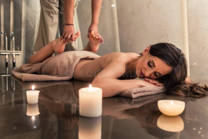 Junge Frau, welche die ausdehnenden Techniken der thailändischen Massage genießt stockbilder