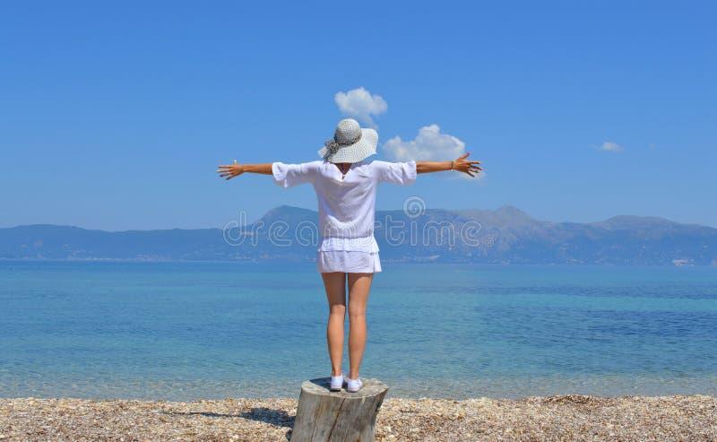 Junge Frau, welche die Berge über Meer mit ihrem Arme wid betrachtet lizenzfreie stockfotos