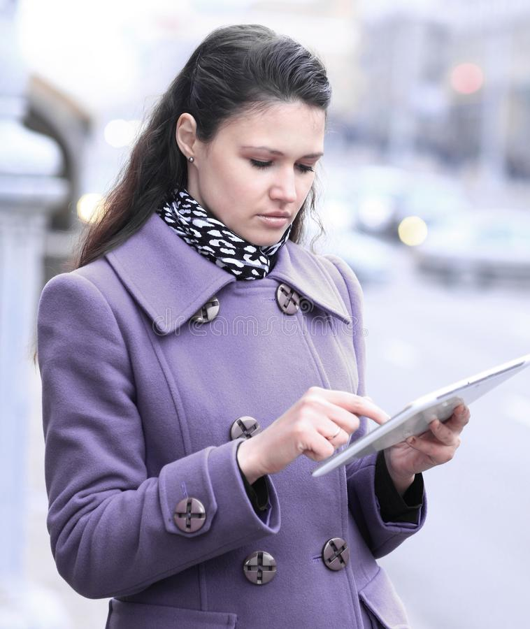 Junge Frau, welche die digitale Tablette steht auf Stadtstraße verwendet stockbild