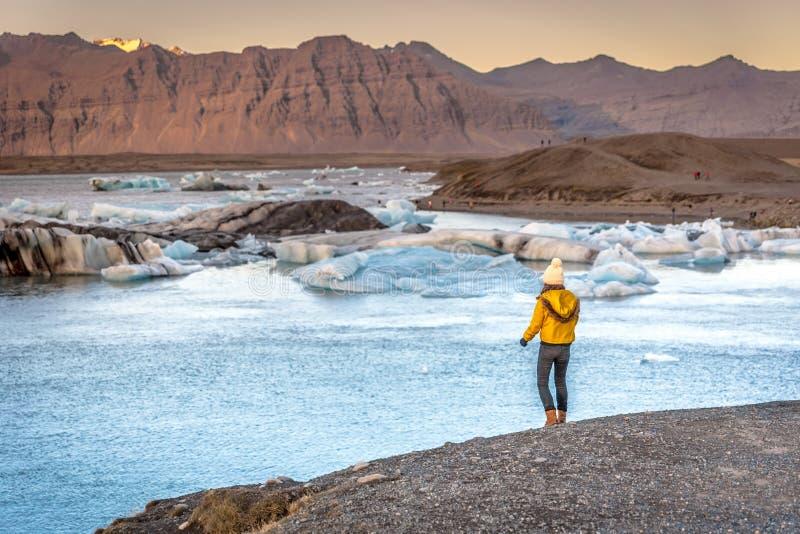 Junge Frau, welche die gelbe kalte Kleidung sieht das erstaunliche Jokulsarlon, Eisberglagune in Island, Berge im Hintergrund kle lizenzfreies stockfoto