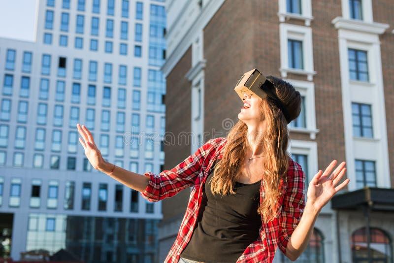 Junge Frau, welche die High-Techen Gläser der virtuellen Realität im Freien verwendet stockbild