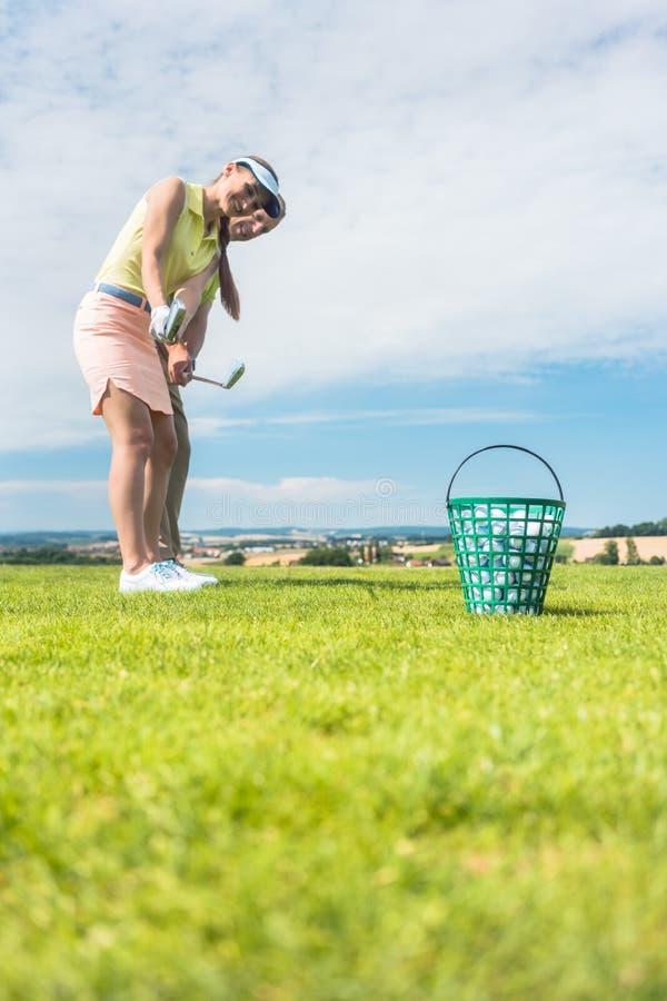 Junge Frau, welche die korrekte Bewegung während der Golfklasse mit übt lizenzfreies stockfoto