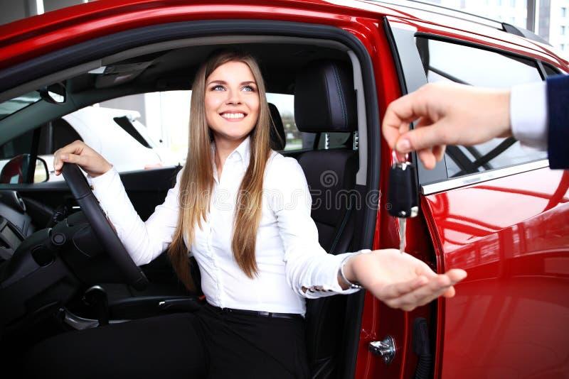 Junge Frau, welche die Schlüssel des Neuwagens empfängt stockfotos