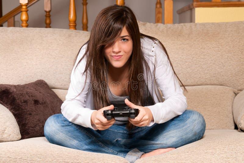 Junge Frau, welche die Videospiele zu Hause sich konzentrieren auf Couch spielt lizenzfreie stockbilder