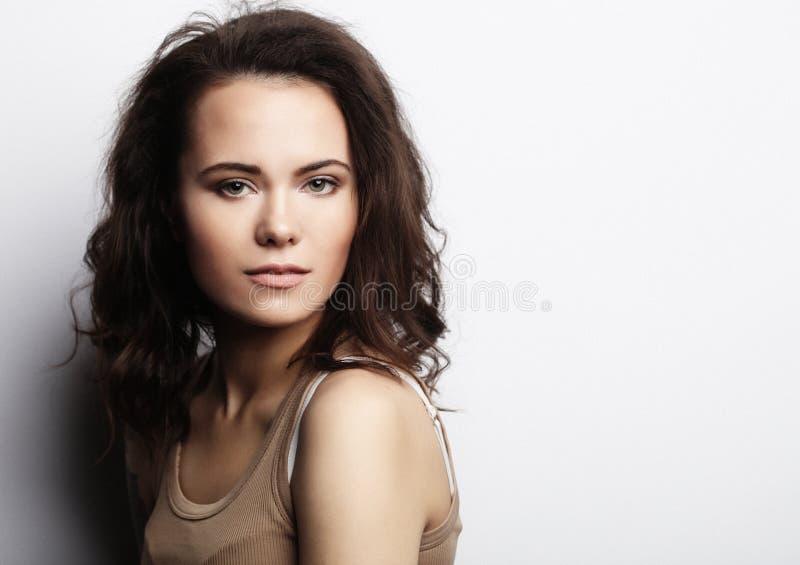 Junge Frau, welche die zufällige Kleidung, werfend auf weißem Hintergrund trägt auf lizenzfreies stockfoto