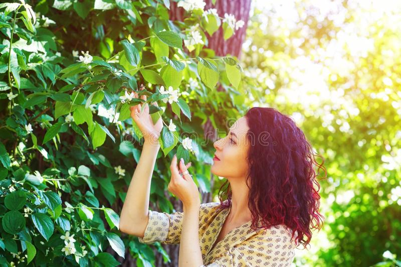 Junge Frau, welche im Frühjahr die Natur an den blühenden Bäumen genießt lizenzfreies stockfoto