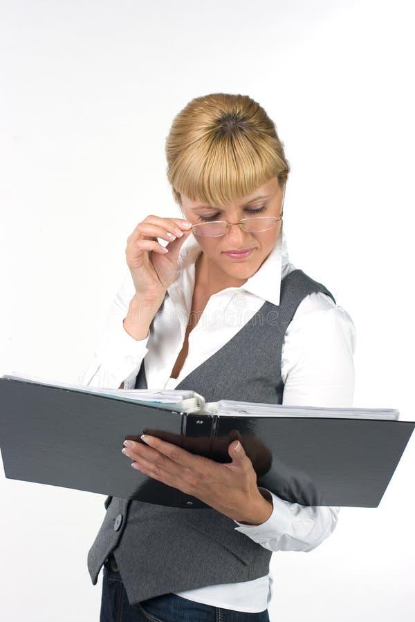 Junge Frau, welche sorgfältig die Dokumente studiert lizenzfreies stockfoto