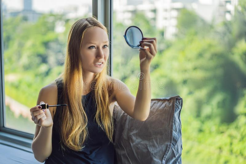 Junge Frau wendet Make-upfront des Fensters in der Sch?nheitsstudiowohnung an Berufsmake-uphaaranreden haut lizenzfreie stockfotografie